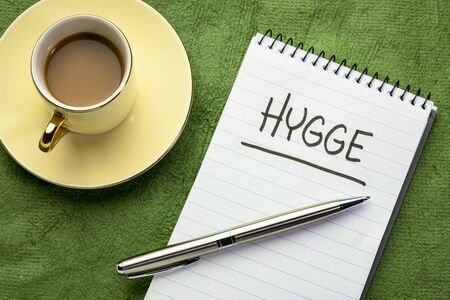Hygge, Danish lifestyle concept - handwriting on a napkin with a cup of coffee.