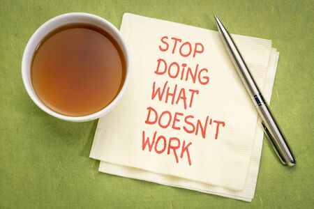Stop doing what does not work - Motivational handwriting on a napkin with a cup of tea