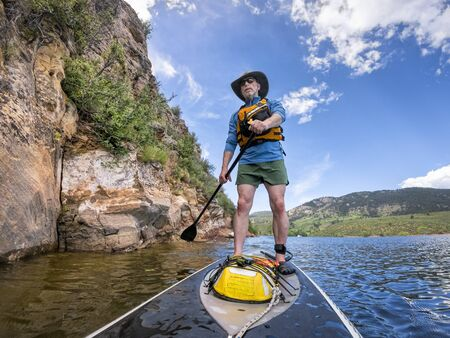 Senior male paddler enjoying workout on a stand up paddleboard - Horsetooth Reservoir in northern Colorado in summer scenery with a high water level 스톡 콘텐츠