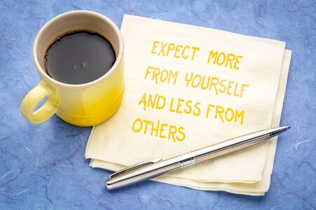 Expect more from yourself and less from others - Inspirational handwriting on a napkin with a cup of coffee