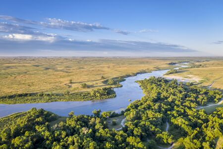 shallow and wide Dismal RIver meandering trough Nebraska Sandhills at Nebraska National Forest, aerial view of summer scenery