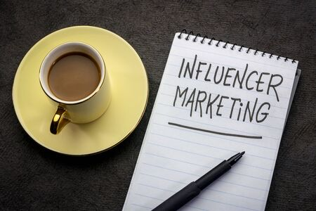 influencer marketing  -  handwriting in a spiral notebook with a cup of tea 写真素材