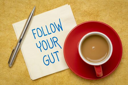 Follow your gut reminder - handwriting on a napkin with a cup of coffee