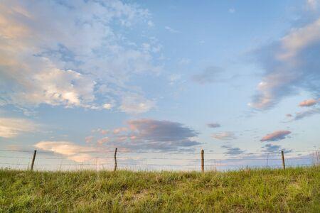 rural landscape of Nebraska Sandhills with a cattle fence
