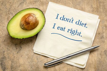 I do not diet, I eat right - inspirational writing on a napkin with a cut avocado.