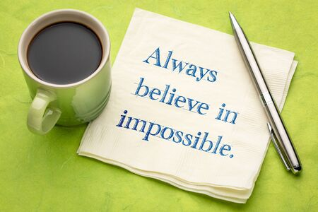 Always believe in impossible inspirational reminder - writing on a napkin with a cup of coffee