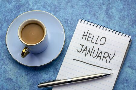 Hello January - handwriting in a notebook with a cup of coffee Stockfoto