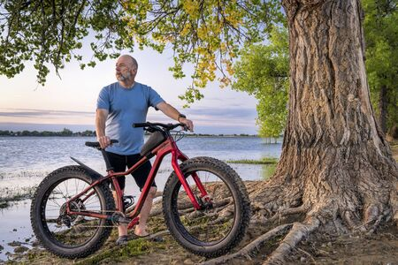 athletic senior man with a fat mountain bike on a lake shore enjoying sunrise - Boyd Lake State Park in northern Colorado Reklamní fotografie