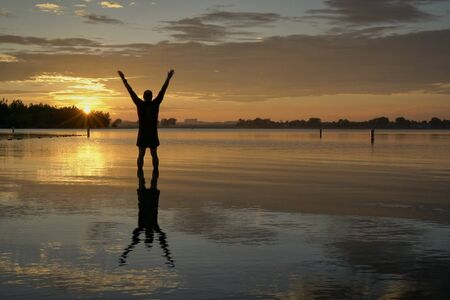 sunrise silhouette of a man standing in shallow water and stretching or practicing chigong movements, Boyd Lake State Park in northern Colorado