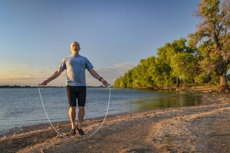 active senior man is jumping a heavy fitness jump rope on a lake beach, Boyd Lake State Park in northern Colorado Banco de Imagens