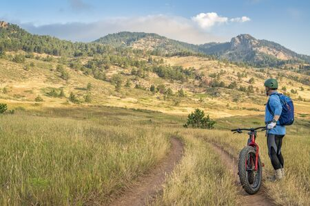 male cyclist with a fat mountain bike enjoying morning view of Rocky Mountains foothills at Lory State Park