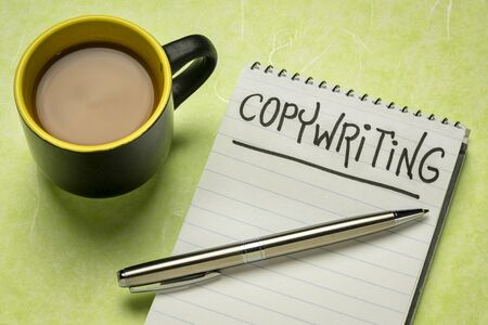 copywriting word - handwriting in a spiral notebooks with a cup of coffee
