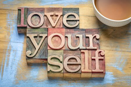 love yourself word abstract in letterpress wood type blocks with a cup of tea