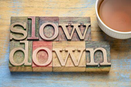 Reducir la velocidad - Resumen de palabras en bloques tipo madera tipográfica con una taza de té