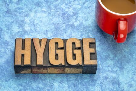 hygge word abstract in vintage letterpress wood type blocks with a cup of coffee, Danish lifestyle concept 스톡 콘텐츠