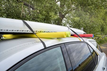 stand up paddleboard on a rental car roof, improvised fitting with straps and swimming pool foam noodles Stock Photo - 129421353