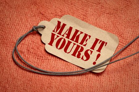 make it yours on a paper price tag with a twine against textured paper, shopping marketing concept