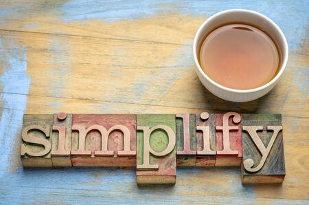 simplify - text in letterpress wood type with a cup of tea, business or lifestyle  minimalism concept Banque d'images