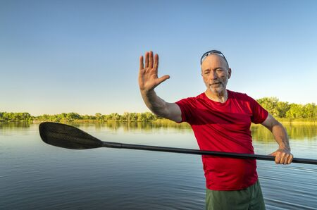 senior male with a stand up paddle on a calm lake in summer afternoon scenery, Fort Collins, Colorado