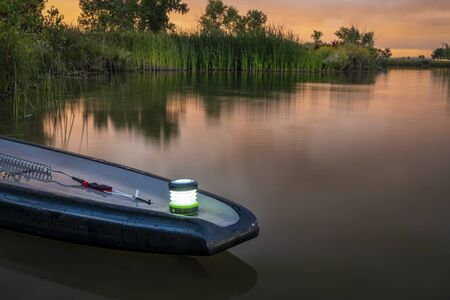 A quiet evening on a lake - tail of stand up paddleboard with a small lantern, recreation concept