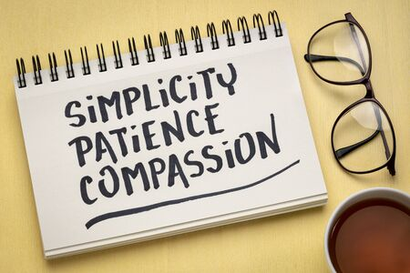 simplicity, patience, compassion - three words from Buddha teaching - handwriting in a notebook with a cup of tea, spiritual wisdom concept