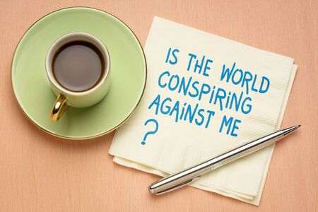 Is the world conspiring against me? A question on a napkin with a cup of coffee. Conspiracy and frustration concept.