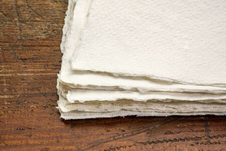 stack of small sheet of blank white Khadi rag paper from South India against rustic wood Фото со стока