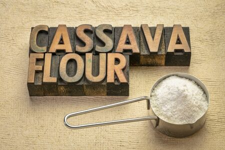 Cassava (yuca) flour in a measuring scoop with a text in vintage wood type. scoop. It is a gluten free and grain free replacement for wheat flour.