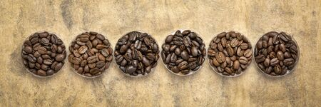 sampler of coffee beans from different parts of the world - overhead view of  round bowls against handmade textured paper with a copy space, long banner format