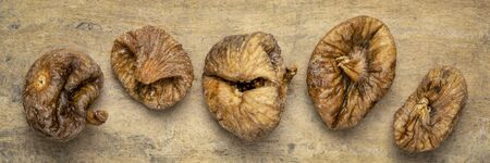dried Turkish figs - row of fruits against textured bark paper, long banner format Stock Photo