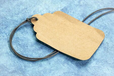 blank paper price tag with a twine against textured blue bark paper