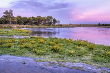 late summer or early fall dusk over Dismal River at Nebraska National Forest with a sandbar covered by yellow widflowers