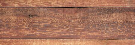 red stained weathered barn wood background with knots and nail holes, rough wooden texture in a long banner format