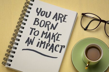 You are born to make an impact - inspiration handwriting in a sketchbook with a cup of coffee, make a difference concept Standard-Bild