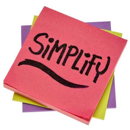 simplify reminder, pragmatic, declutter or get organized concept,  - black ink handwriting on an isolated sticky note