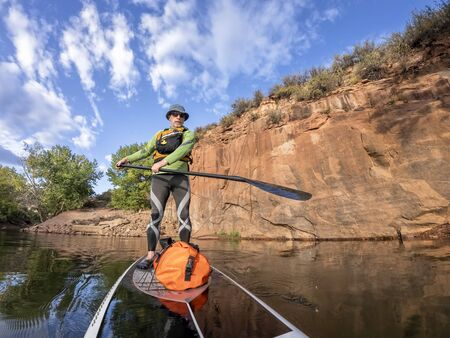 senior man paddling a stand up paddleboard a mountain lake with sandstone cliffs - Horsetooth Reservoir , COlorado, in early fall scenery