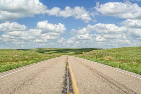 rural highway across Nebraska Sandhills on a sunny summer day, travel or journey concept Stock Photo