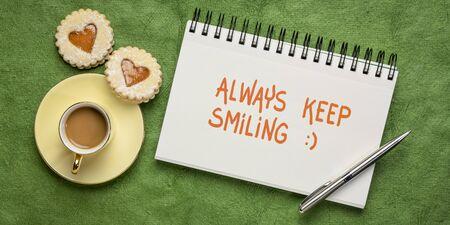 continua sempre a sorridere con una calligrafia ispiratrice in un album da disegno, piatto con caffè e biscotti al cuore, ottimismo, gentilezza e concetto di positività