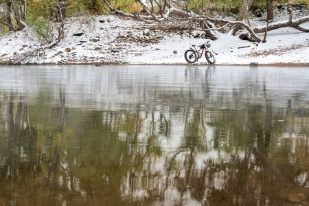 mountain fat bike on a lake shore in fall scenery with snow, Horsetooth Reservoir in northern Colorado