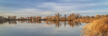 panorama of calm lake in fall scenery with reeds and cottonwood trees, northern Colorado Imagens