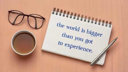 the world is bigger than you got to experience - inspirational quote in a sketchbook with a cup of tea