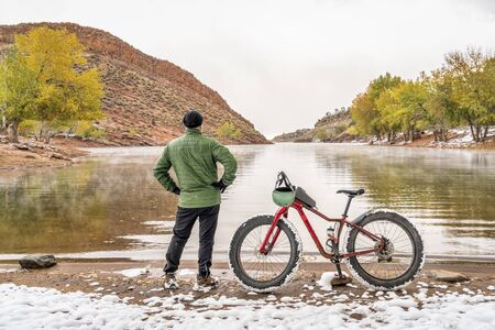 senior male cyclist with a mountain fat bike on a lake shore in fall scenery, Horsetooth Reservoir in foothills of northern Colorado Imagens