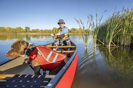 senior male is paddling canoe with a pit bull  dog in a life jacket, calm lake in Colorado in fall scenery