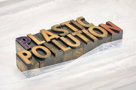 plastic pollution typography and concept - text in vintage letterpress wood type against sheets of plastics, throw-away culture