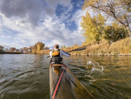 senior male paddler is paddling a long, narrow and fast racing sea kayak on  a calm lake, fall scenery in Colorado, POV from a kayak stern