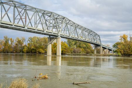 Brownville Bridge built in 1939  is a truss bridge over the Missouri River on U.S. Route 136  from Nemaha County, Nebraska, to Atchison County, Missouri, at Brownville, Nebraska, fall scenery with high water flow.