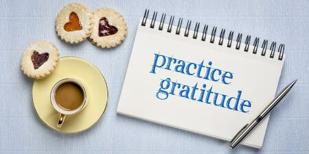 practice gratitude inspirational text in sketchbook with a cup of coffee and heart cookies