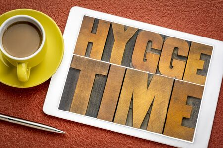 hygge time  word abstract in vintage letterpress wood type on a digital tablet with coffee, Danish lifestyle concept