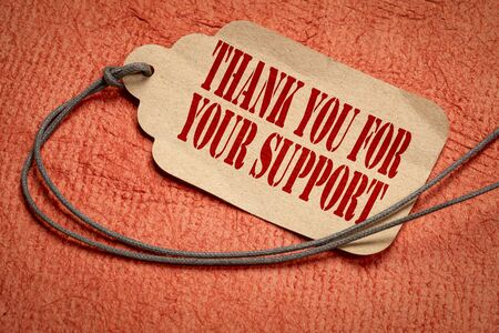 thank your for your support  on a paper price tag with a twine against textured orange bark paper