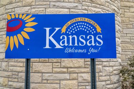 Kansas welcomes you - welcome roadside sign at freeway rest area with a popular Latin phrase ad astra per aspera (through hardships to the stars), driving and travel concept